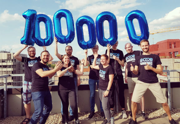 Seobility Team celebrates the 100,000th user. You can see the Seobility Team in summer 2019, holding up the number 100,000 as a balloon.